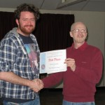 Patrick Donnelly receiving his First Place certificate from Tremaine Cornish