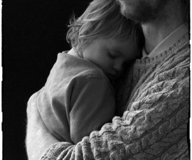 Photo by Mal Holmes.    Molly sleeping in her father's arms  as he conducts his Curator Tour of the new Exhibition in the Open Eye Gallery.